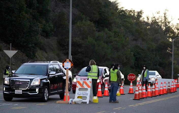 Drivers with a vaccine appointment enter a mega COVID-19 vaccination site set up in the parking lot of Dodger Stadium in Los Angeles Saturday, Jan. 30, 2021. One of the largest vaccination sites in the country was temporarily shut down Saturday because dozen of protesters blocked the entrance.