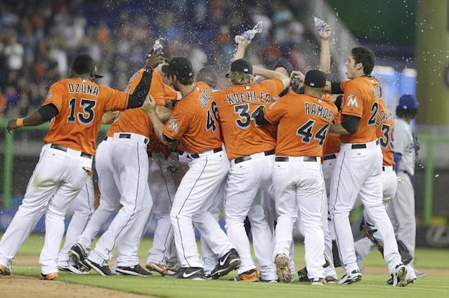 Miami Marlins players mob Jeff Baker, after he hit a double that scored Adeiny Hechavarria, during the ninth inning of a baseball game against the Los Angeles Dodgers, Sunday, May 4, 2014 in Miami. The Marlins defeated the Dodgers 5-4. (AP Photo/Wilfredo Lee)