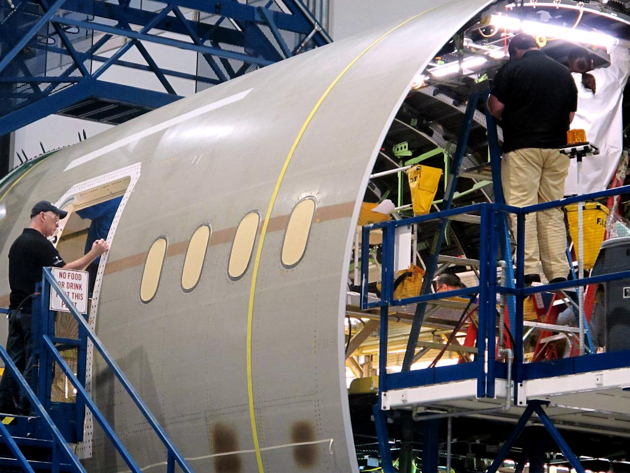 Workers assemble the aft section of Boeing's new 787 aircraft at the company's plant in North Charleston, S.C., on Friday, April 27, 2012. The company was rolling out the first of its new 787s manufactured at its South Carolina plant which opened last year. (AP Photo/Bruce Smith)
