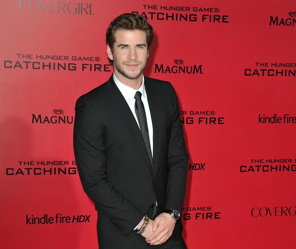 """FILE - In this Monday, Nov. 18, 2013 file photo, Liam Hemsworth arrives at the Los Angeles premiere of """"The Hunger Games: Catching Fire,"""" held at the Nokia Theatre LA Live. The actor says he is, """"More comfortable in my own skin than I've ever been in my whole life."""" Returning as Gale Hawthorne in the film releasing in theaters on Friday, Nov. 22, 2013, Hemsworth said hanging with the film's crew, especially co-star Jennifer Lawrence, also helps him stay positive. (Photo by Jordan Strauss/Invision/AP)"""