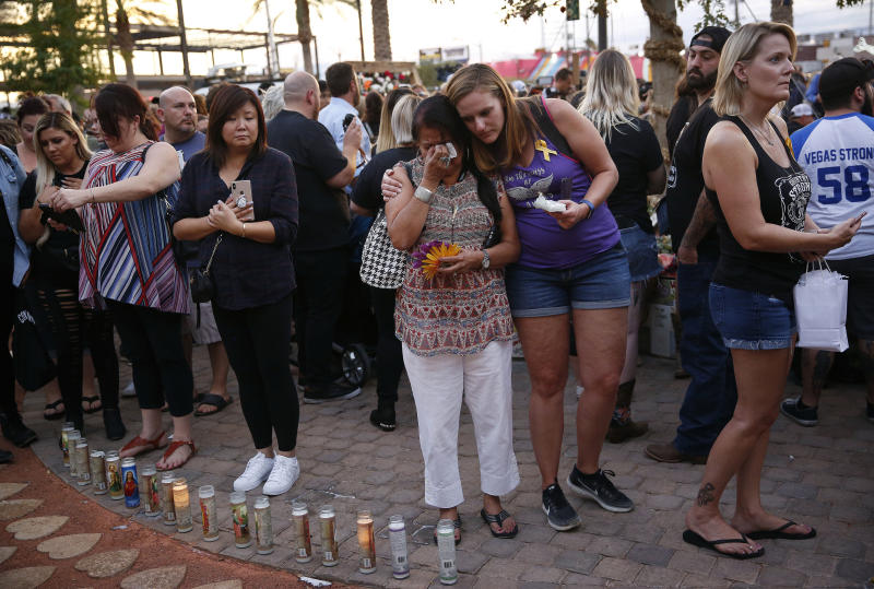 FILE - In this Monday, Oct. 1, 2018 file photo people embrace before a ceremony at a memorial garden, on the anniversary of the mass shooting a year earlier, in Las Vegas. Two years after a shooter rained gunfire on country music fans from a high-rise Las Vegas hotel, MGM Resorts International reached a settlement that could pay up to $800 million to families of the 58 people who died and hundreds of others who were injured, attorneys announced Thursday, Oct. 3, 2019. (AP Photo/John Locher,File)