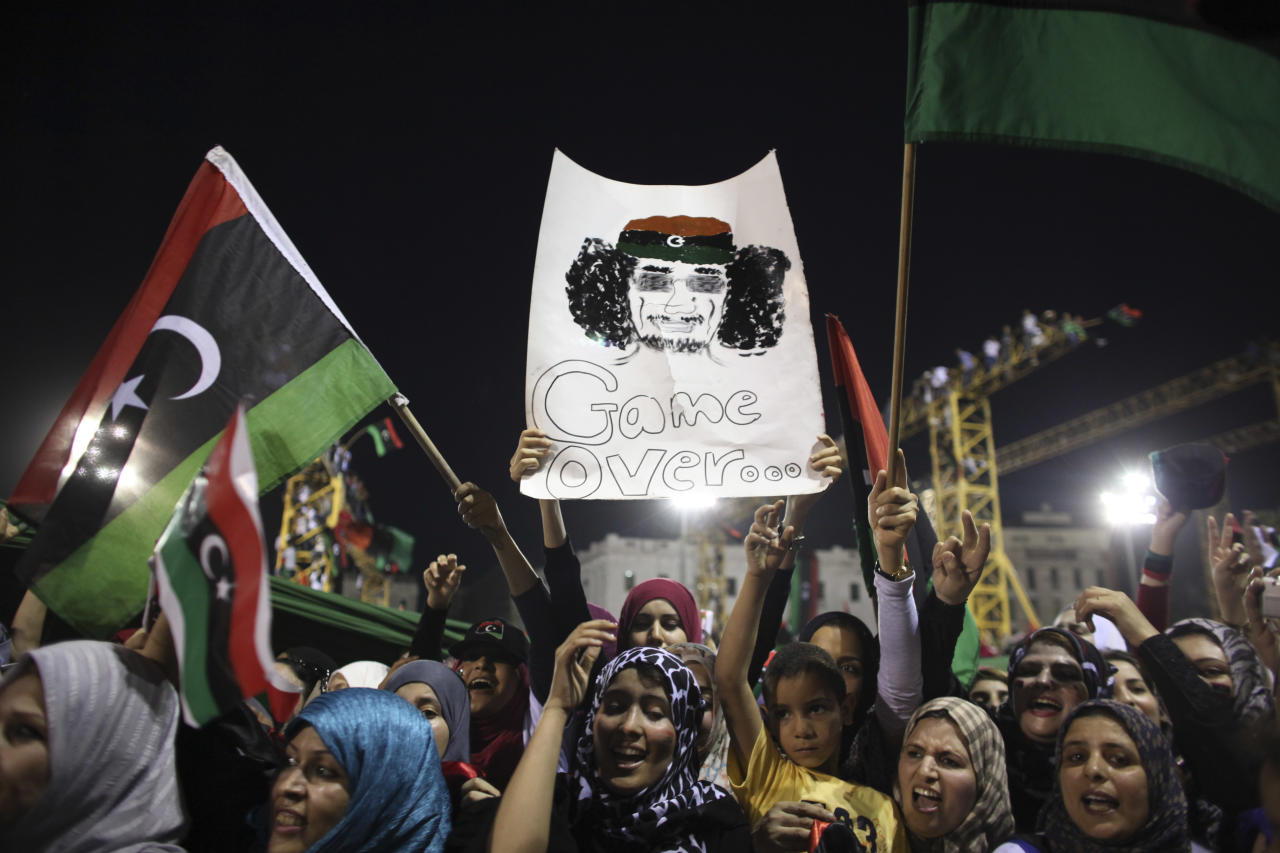 Women celebrate the revolution against Moammar Gadhafi's regime and ask for more women's rights, as they hols a banner depicting Moammar Gadhafi, Tripoli, Libya, Friday, Sept. 2, 2011. Rebel forces are advancing toward Moammar Gadhafi's hometown Sirte despite the extension of a deadline for the town's surrender, rebel officials said Friday, as a U.N. official warned that Libya faces critical but short-term shortages of drinking water, food and other supplies. (AP Photo/Alexandre Meneghini)