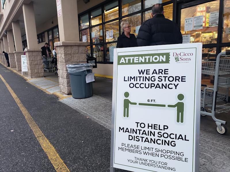 Shoppers line up at a grocery store in Ardsley, NY early Friday morning, March 20, 2020. The store is limiting shoppers and attempting to enforce social distancing.