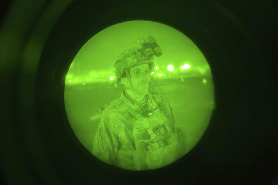 In this image provided by the U.S. Army, made with a night vision scope, Maj. Gen. Chris Donahue, commander of the U.S. Army 82nd Airborne Division, XVIII Airborne Corps, prepares to board a C-17 cargo plane at Hamid Karzai International Airport in Kabul, Afghanistan, Monday, Aug. 30, 2021, as the final American service member to depart Afghanistan. (Master Sgt. Alexander Burnett/U.S. Army via AP)