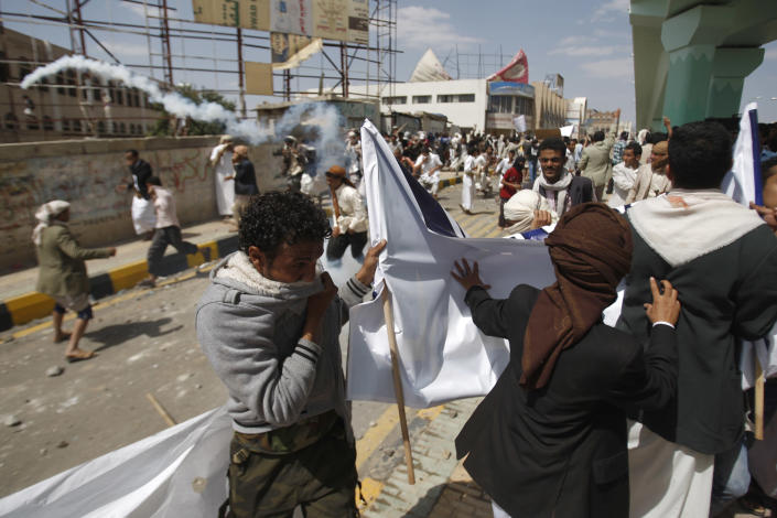 Protesters run from tear gas released by riot police during clashes near the U.S. Embassy in Sanaa, Yemen, Friday, Sept. 14, 2012, as part of widespread anger across the Muslim world about a film ridiculing Islam's Prophet Muhammad. (AP Photo/Hani Mohammed)