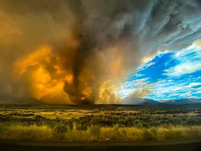 This photo provided by Katelynn & Jordan Hewlett, a funnel appears in a thick plume of smoke from the Loyalton Fire is seen in Lassen County, Calif., Saturday, Aug. 15, 2020. A wildfire in Northern California on Saturday spawned at least one fire tornado that prompted the National Weather Service to issue a tornado warning. The Loyalton Fire in Lassen County, Calif., burned intensely amid hot and dry conditions on Saturday afternoon. (Katelynn & Jordan Hewlett via AP)