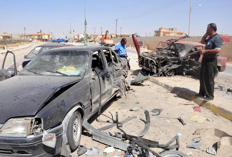 Iraqis inspects the remains of a car after a motorcycle detonated in front of a gas station in a southern district of the northern oil-hub city of Kirkuk, on July 10, 2014