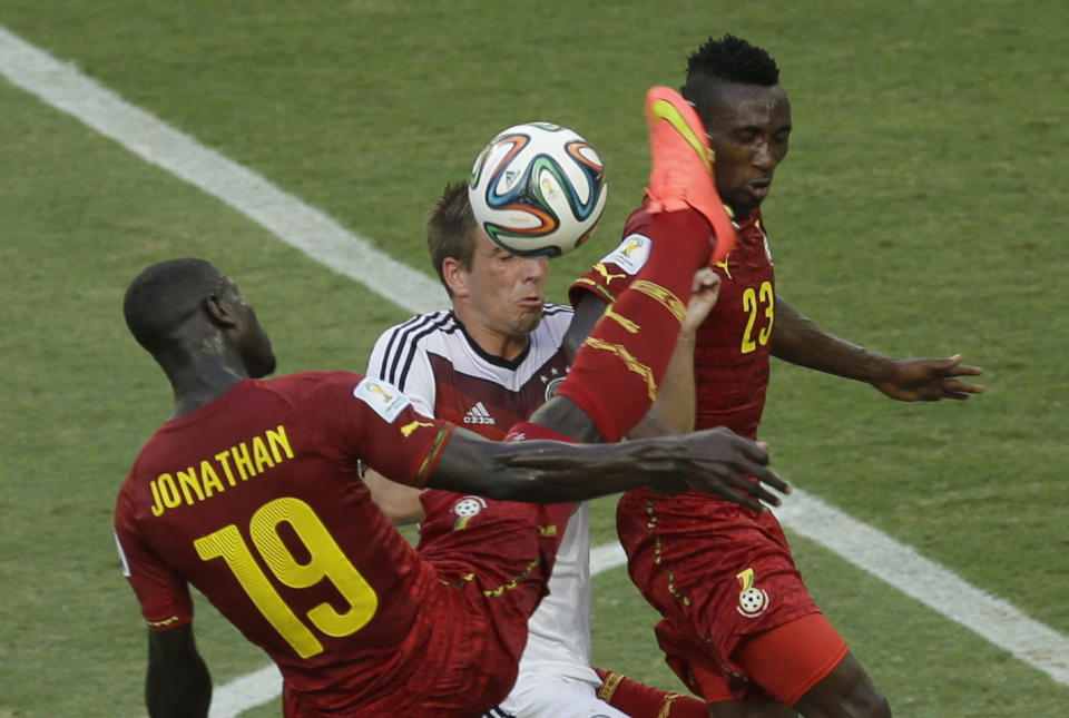 Germany's Philipp Lahm, center, attempts to head the ball under pressure from Ghana's Jonathan Mensah, left, and Harrison Afful during the group G World Cup soccer match between Germany and Ghana at the Arena Castelao in Fortaleza, Brazil, Saturday, June 21, 2014. (AP Photo/Themba Hadebe)
