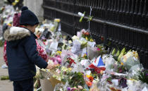 A child looks at flowers left outside the gates of Buckingham Palace in London, a day after the death of Britain's Prince Philip, Saturday, April 10, 2021. Britain's Prince Philip, the irascible and tough-minded husband of Queen Elizabeth II who spent more than seven decades supporting his wife in a role that mostly defined his life, died on Friday. (AP Photo/Alberto Pezzali)