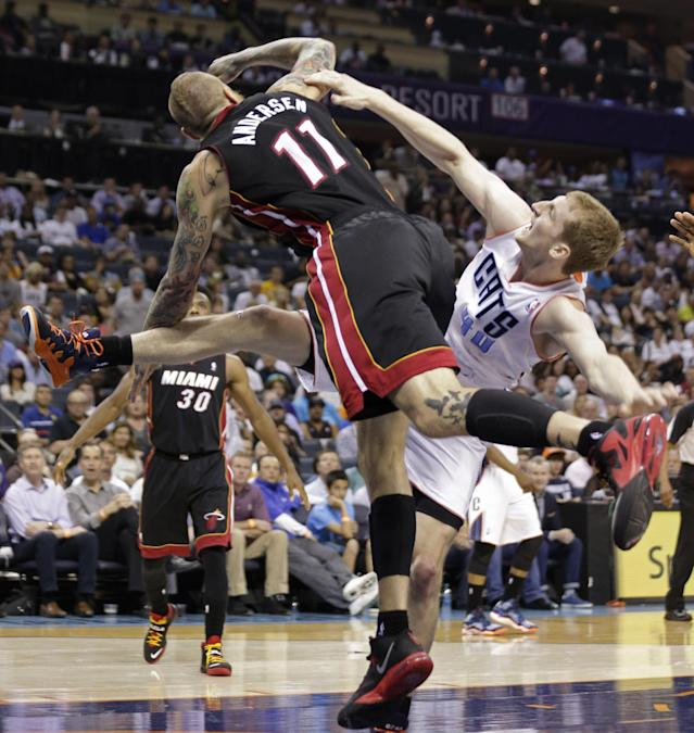 Charlotte Bobcats' Cody Zeller, right, falls as he is fouled by Miami Heat's Chris Andersen, left, during the first half in Game 4 of an opening-round NBA basketball playoff series in Charlotte, N.C., Monday, April 28, 2014. (AP Photo/Chuck Burton)