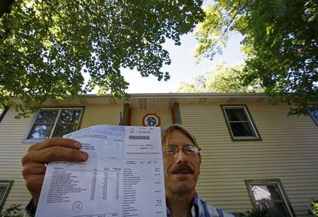 Dan Koivisto poses with a copy of his 2013 property tax bill at his home in Ingleside, Illinois, United States, July 30, 2015. REUTERS/Jim Young