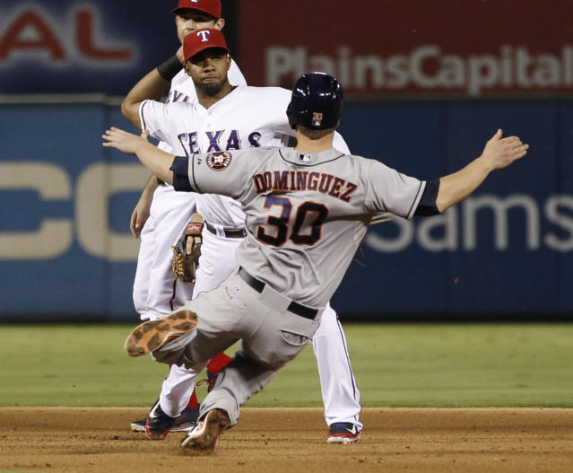 Texas Rangers shortstop Elvis Andrus throws to first base after forcing out Houston Astros' Matt Dominguez (30) during the seventh inning of a baseball game, Wednesday, Aug. 21, 2013, in Arlington, Texas. Max Stassi was out at first. (AP Photo/Jim Cowsert)