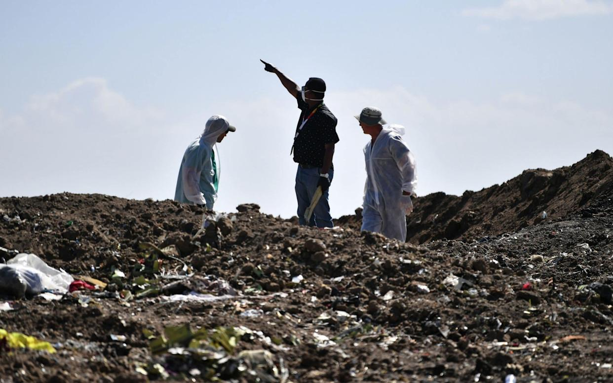 Investigators inspect the crash site of the Ethiopian Airlines plane, which went down on March 10 - AFP