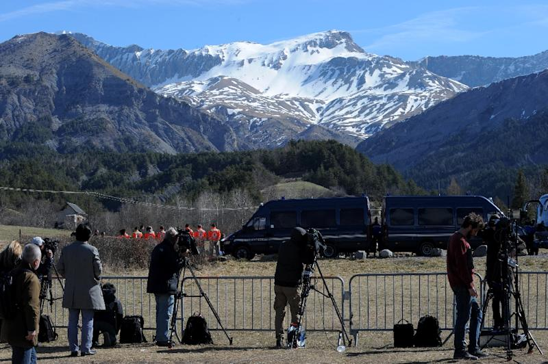 Police vans block the view as Japanese victims pay their respects on March 29, 2015 near a commemorative headstone in Seyne-les-Alpes, the closest accessible area to where a Germanwings flight crashed in the French Alps (AFP Photo/Jean-Pierre Clatot)