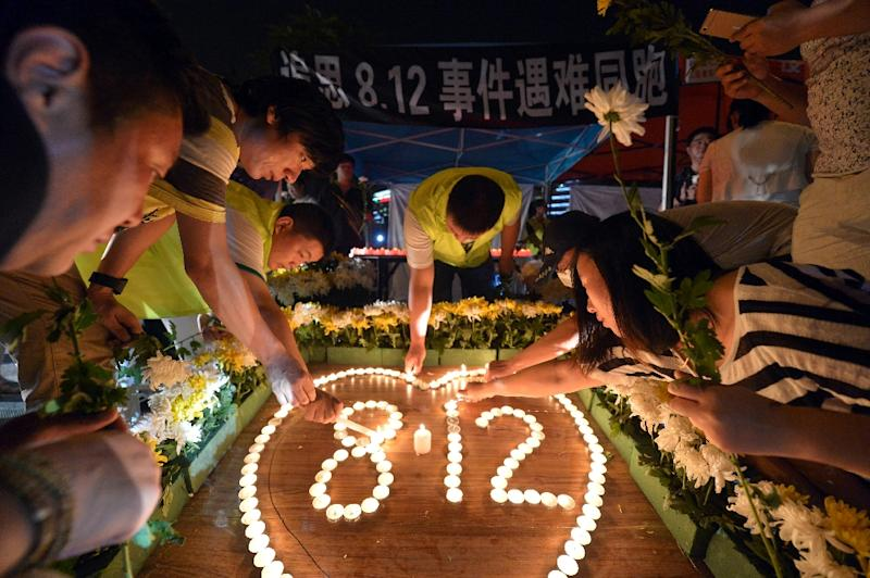Residents lighting candles at the crossroads outside Tianjin Taida hospital at a vigil for the victims of the explosions at a chemical warehouse in Tianjin on August 16, 2015 (AFP Photo/STR)