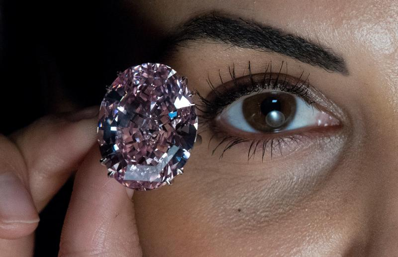 "A model poses with a 59.60-carat oval mixed-cut pink diamond, known as ""The Pink Star"", during a photocall at Sotheby's auction house in London on March 20, 2017, to promote its forthcoming auction. The diamond, with an estimated value of 48.5 million GBP (60 million euros; 60 million USD), is said to be the largest Internally Flawless Fancy Vivid Pink diamond that the Gemological Institute of America (GIA) has ever graded, and is set to be auctioned in Hong Kong on April 4, 2017. / AFP PHOTO / Justin TALLIS (Photo credit should read JUSTIN TALLIS/AFP via Getty Images)"