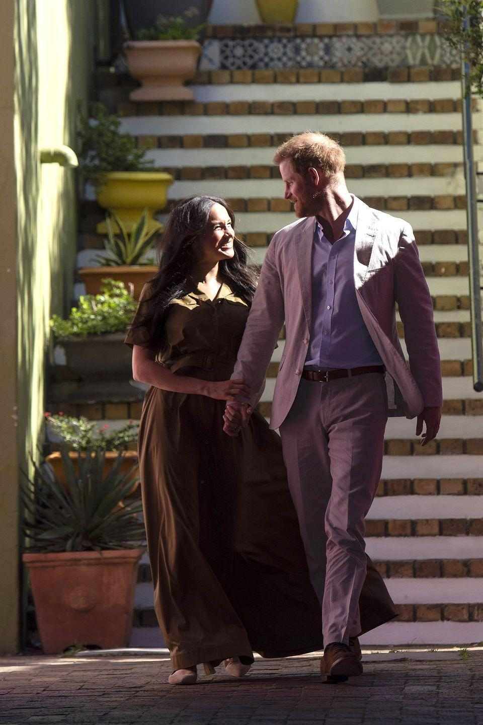 <p>Meghan smiles brightly while holding hands with Harry as they visit the oldest mosque of Cape Town in Dorp Street in Bo Kaap district.</p>