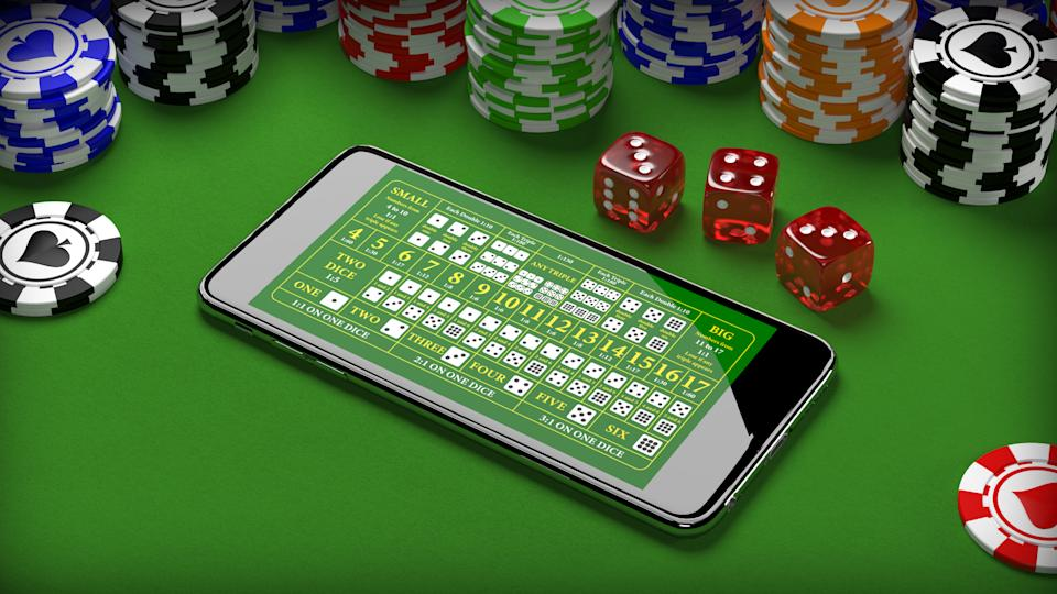 Online casino with smartphone, poker chips and dice. (Photo: Getty Images)