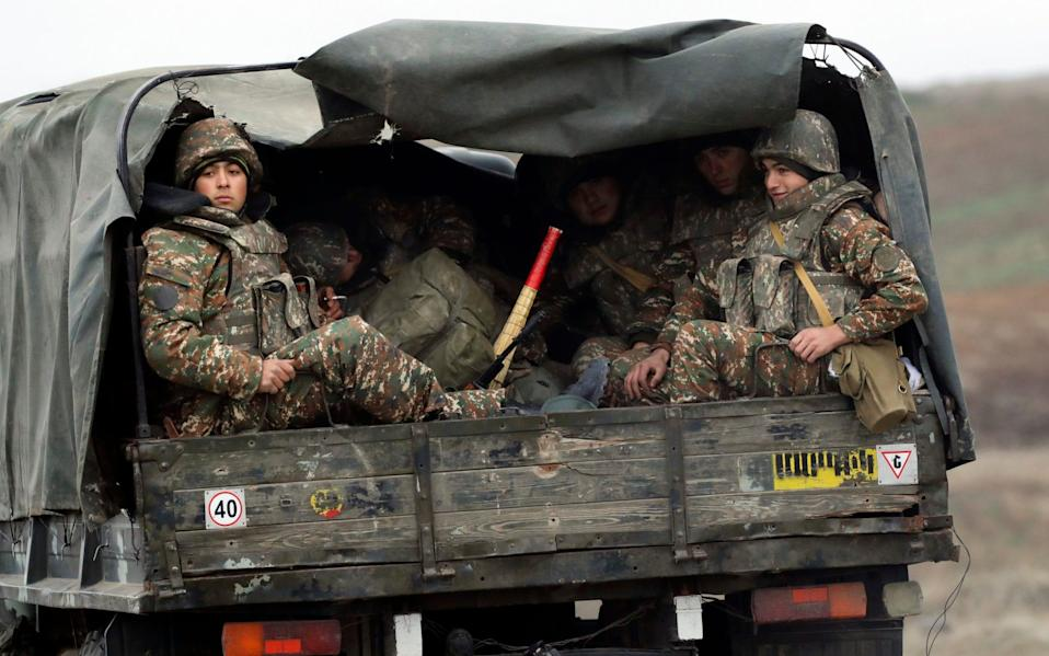 Ethnic Armenian soldiers sit in a military truck on a road during the withdrawal of Armenian troops from the separatist region of Nagorno-Karabakh - AP