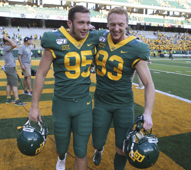 Baylor place kicker John Mayers (L) walks off with teammate Russell Morrison after defeating Iowa State in the second half of an NCAA college football game, Saturday, Sept. 28, 2019, in Waco, Texas. Mayers had the game-winning field goal late in the game. (AP)