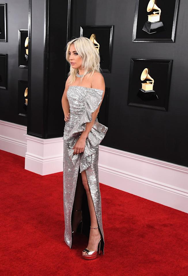 "<p>Wearing <a rel=""nofollow"" href=""https://www.popsugar.com/fashion/Lady-Gaga-Celine-Dress-2019-Grammys-45774303"">a silver</a> Celine dress with dramatic ruffles. She accessorized with Tiffany & Co. jewels and Jimmy Choo heels.</p>"