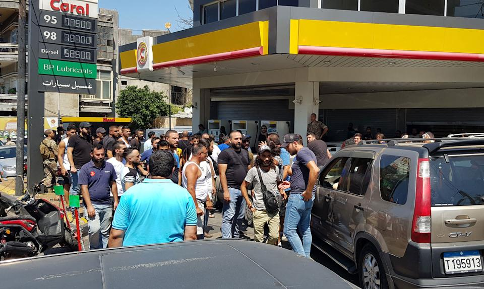 People line up outside of a gas station to fill their vehicles in Tripoli, Lebanon
