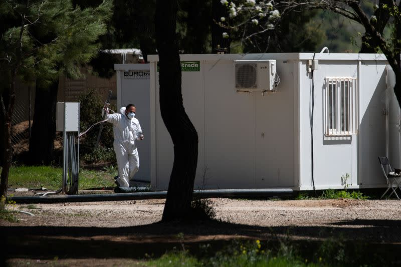 A man wearing a protective suit and a face mask makes his way in the Ritsona migrant camp after authorities found 20 coronavirus cases and placed the camp under quarantine, following the outbreak of coronavirus disease (COVID-19), in Ritsona
