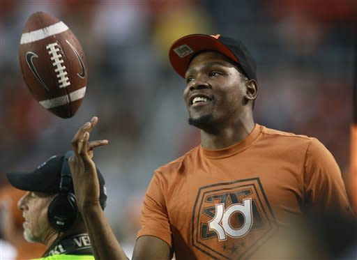 Oklahoma City Thunder's Kevin Durant, who attended the University of Texas, tosses a football around on the sidelines during the first quarter of an NCAA college football game between Oklahoma State and Texas in Stillwater, Okla., Saturday, Sept. 29, 2012. Texas won 41-36. (AP Photo/Sue Ogrocki)