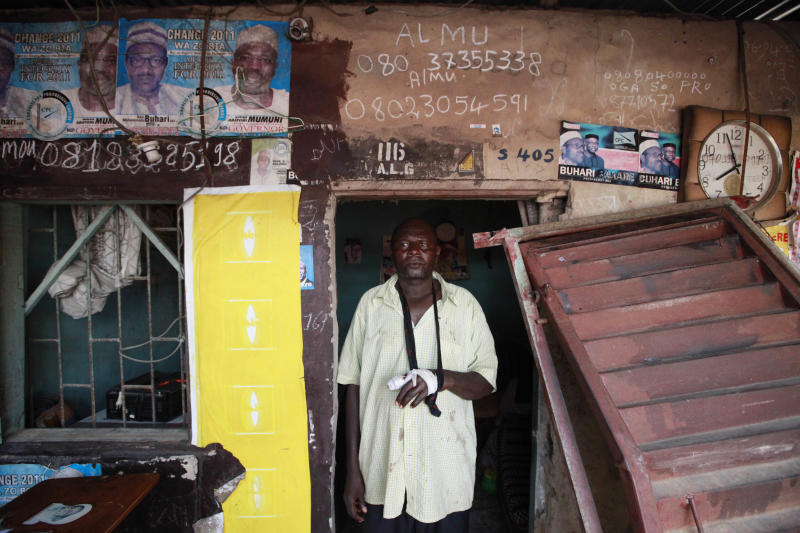 In this photo taken Friday, April. 12, 2013 Yushau Ibrahim, stands outside his shop with an injured arm after security force raided and stole nearly $10,000 at Katangua market in Lagos, Nigeria. The buses crammed full of young men leave each afternoon from this busy market in Nigeria's largest city, some with bruises around their faces and defensive wounds to their arms. The immigrant labor that makes Katangua Market in Lagos thrum along each day between piles of secondhand clothes and down narrow dirt alleyways remains in fear after a series of raids by Nigerian authorities in recent days. Immigrant workers here and elsewhere, those largely from neighboring Niger to the north, find themselves targeted by security agencies anxious about a growing Islamic extremist insurgency in Nigeria that could spread southward. (AP Photo/Sunday Alamba)