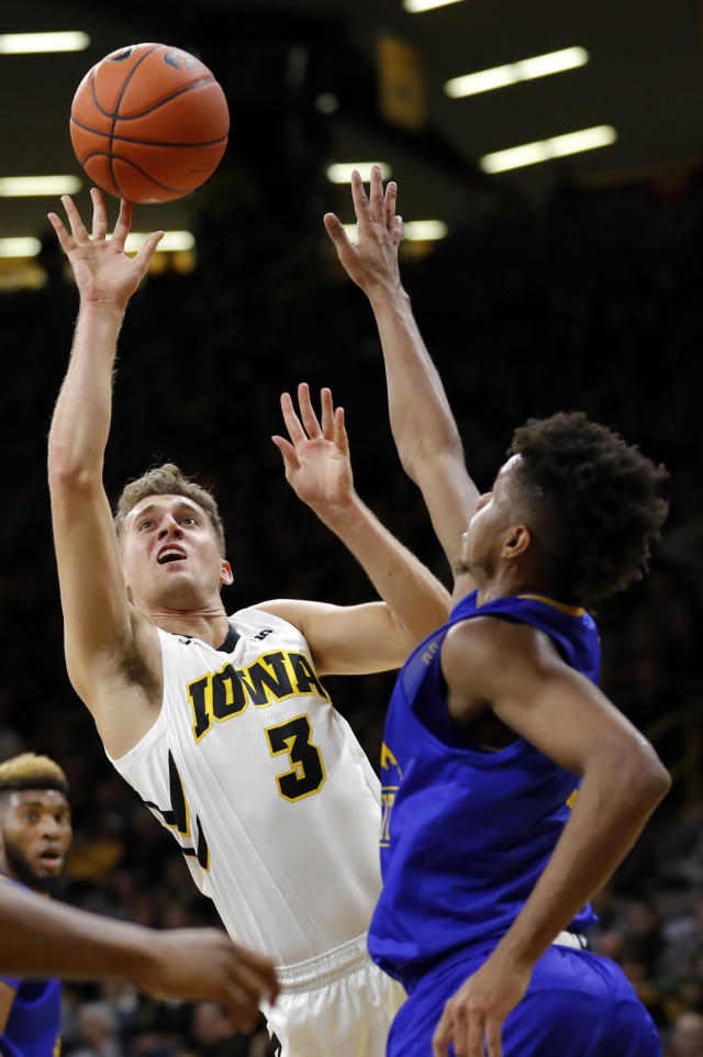 Iowa guard Jordan Bohannon (3) drives to the basket over UKMC guard Rob Whitfield, right, during the first half of an NCAA college basketball game, Thursday, Nov. 8, 2018, in Iowa City, Iowa.(AP Photo/Charlie Neibergall)