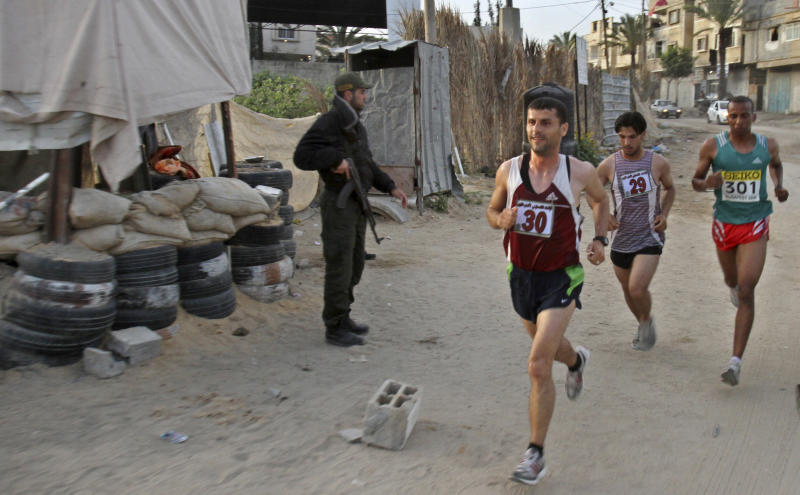 Palestinian Omar Abu Said, left, Azmi Majaideh, center, and  Husam Naseir, right, participate in the first Gaza marathon run past a Hamas security officer manning a checkpoint in Beit Lahiya, northern Gaza Strip, Thursday, May 5, 2011. According to UN estimates some 1,500 people attended the event, running from Beit Hanoun in the northern Gaza Strip, to Rafah in the south.  (AP Photo/Adel Hana)