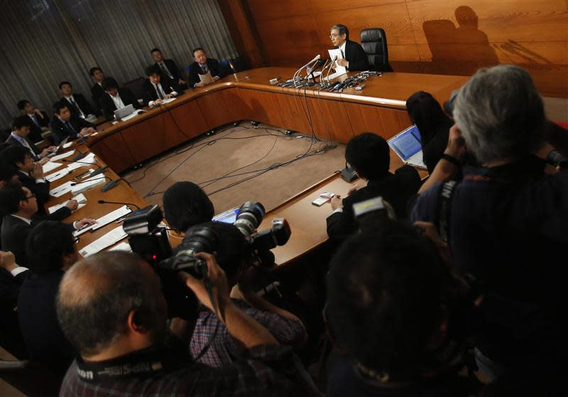 Photographers take pictures of Bank of Japan Governor Kuroda holding his documents during a news conference at the BOJ headquarters in Tokyo