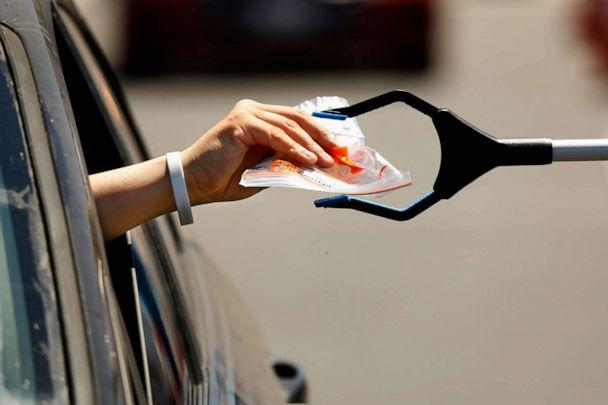 PHOTO: A test kit is passed through the car window at the Anaheim Convention Center in Anaheim, Calif, July 11, 2020. (Carolyn Cole/Los Angeles Times via Getty Images)