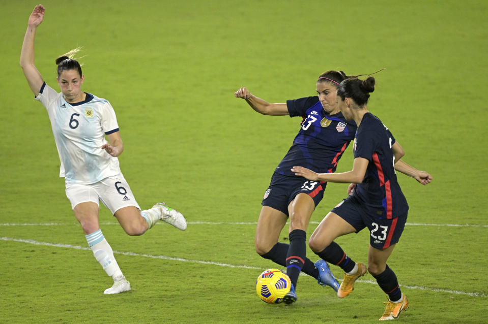 United States forward Alex Morgan (13) scores a goal between forward Christen Press (23) and Argentinal defender Aldana Cometti (6) during the second half of a SheBelieves Cup women's soccer match, Wednesday, Feb. 24, 2021, in Orlando, Fla. (AP Photo/Phelan M. Ebenhack)