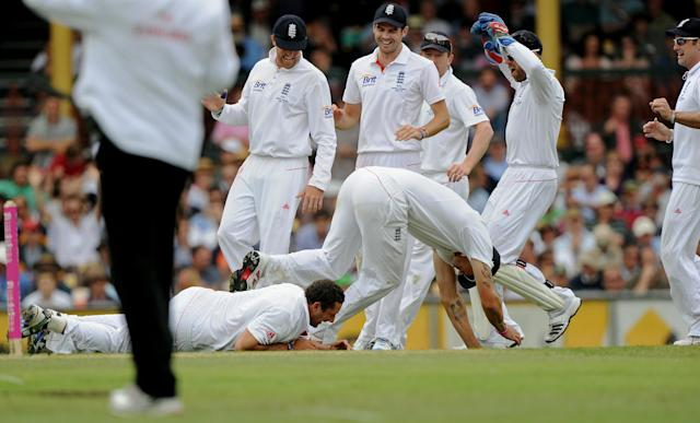 England's Tim Bresnan (below-L) and teammate Kevin Pietersen (below-R) fall over each other after Bresnan took the wicket of Australia's Michael Clarke on day one of the fifth Ashes cricket Test at the Sydney Cricket Ground on January 3, 2011. Clarke was out for four runs. IMAGE STRICTLY RESTRICTED TO EDITORIAL USE - STRICTLY NO COMMERCIAL USE AFP PHOTO / Greg WOOD (Photo credit should read GREG WOOD/AFP/Getty Images)