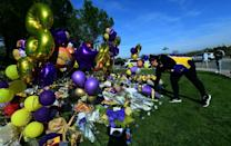 A Lakers fan lays flowers at a makeshift memorial outside the gated community to the late NBA great Kobe Bryant's home (AFP Photo/Frederic J. BROWN)