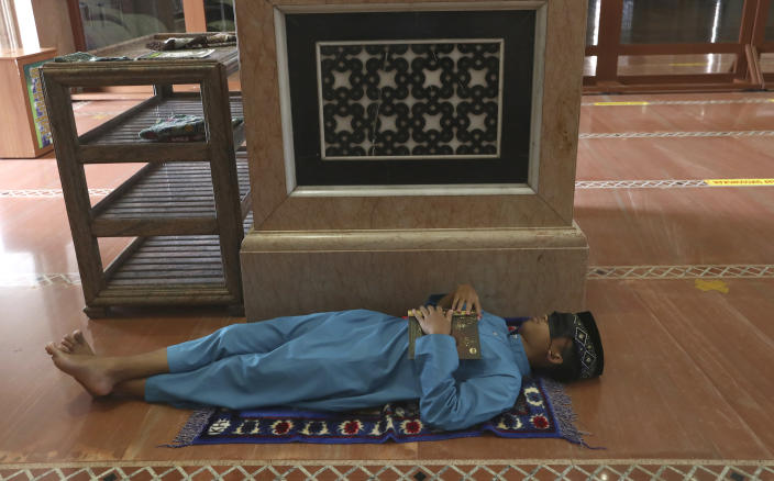 A man takes a nap while waiting for the time to break his fast at the Kubah Mas mosque in Depok, Indonesia, Friday, April 16, 2021. (AP Photo/Tatan Syuflana)