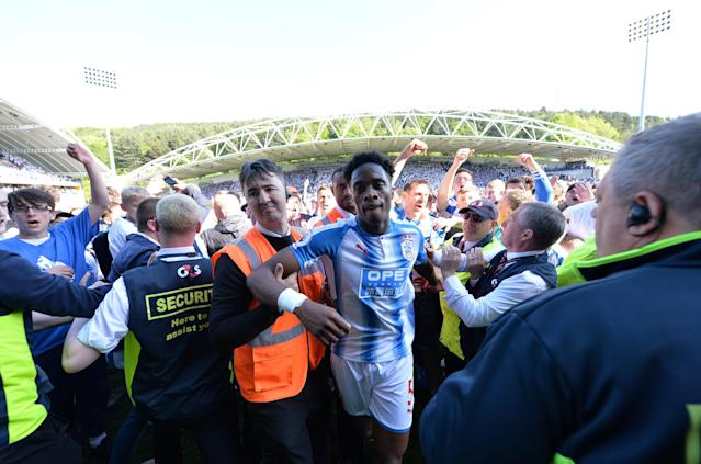 "Soccer Football - Premier League - Huddersfield Town vs Arsenal - John Smith's Stadium, Huddersfield, Britain - May 13, 2018 Huddersfield Town's Terence Kongolo celebrates with fans on the pitch at the end of the match REUTERS/Peter Powell EDITORIAL USE ONLY. No use with unauthorized audio, video, data, fixture lists, club/league logos or ""live"" services. Online in-match use limited to 75 images, no video emulation. No use in betting, games or single club/league/player publications. Please contact your account representative for further details."