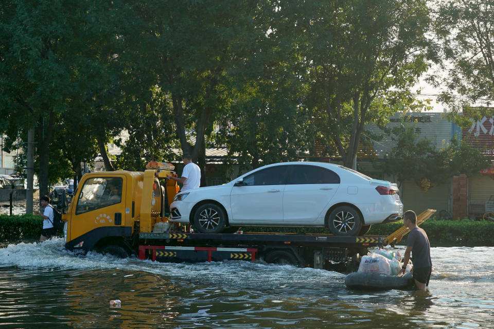 A tow truck drives along a flooded street in Xinxiang in central China's Henan Province, Monday, July 26, 2021. Forecasters Monday said more heavy rain is expected in central China's flood-ravaged Henan province, where the death toll continues to rise after flash floods last week that killed dozens of people. (AP Photo/Dake Kang)