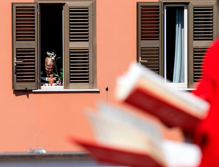 A resident reacts as she watches from her appartment Palm Sunday mass celebrated (R) on the rooftop of the San Gabriele dell'Addolorata church in Rome on April 5, 2020, during the country's lockdown aimed at curbing the spread of the COVID-19 infection.