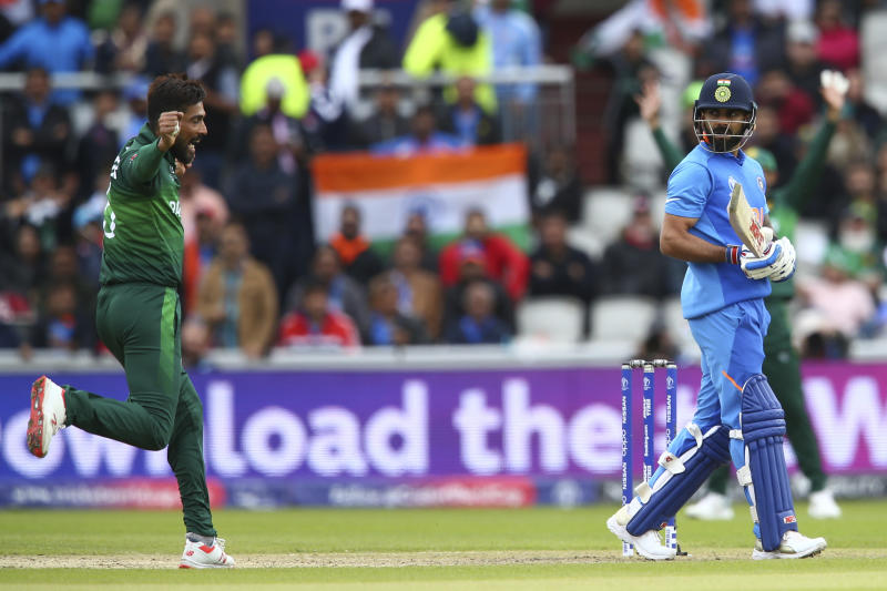 India's captain Virat Kohli, right, leaves the pitch after he is caught by Pakistan's captain Sarfaraz Ahmed off the bowling of Pakistan's Mohammad Amir, left, during the Cricket World Cup match between India and Pakistan at Old Trafford in Manchester, England, Sunday, June 16, 2019. (AP Photo/Dave Thompson)