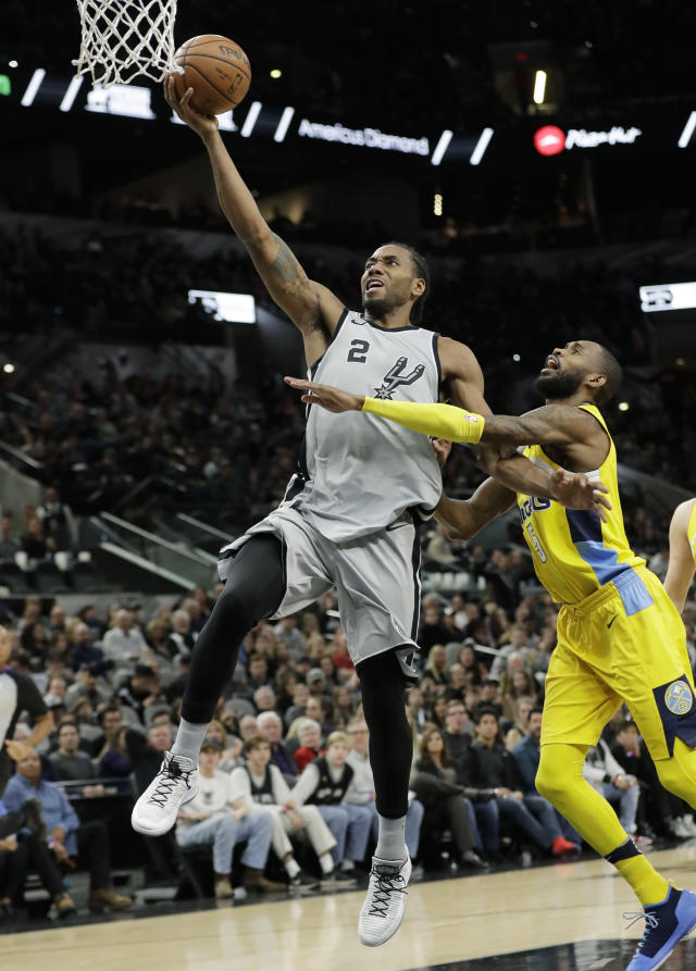 FILE - In this Jan. 13, 2018, file photo, San Antonio Spurs forward Kawhi Leonard (2) scores past Denver Nuggets guard Will Barton (5) during the second half of an NBA basketball game, in San Antonio. Two people familiar with the situation say San Antonio and Toronto have reached an agreement in principle on a trade that will send Kawhi Leonard to the Raptors and DeMar DeRozan to the Spurs. One of the people says the Spurs also are sending Danny Green to the Raptors as part of the deal. Both people spoke to The Associated Press on condition of anonymity Wednesday, July 18, 2018, because the deal has not been finalized. (AP Photo/Eric Gay, File)