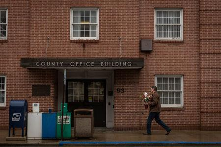 A man carries flowers outside a county office on Valentine's Day in Waynesburg, Pennsylvania, U.S., February 14, 2018. Picture taken February 14, 2018. REUTERS/Maranie Staab