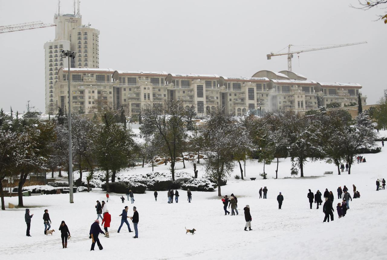 People visit a park after a snowstorm in Jerusalem December 12, 2013. Snow fell in Jerusalem and parts of the occupied West Bank where schools and offices were widely closed and public transport was paused. REUTERS/Amir Cohen (JERUSALEM - Tags: ENVIRONMENT)