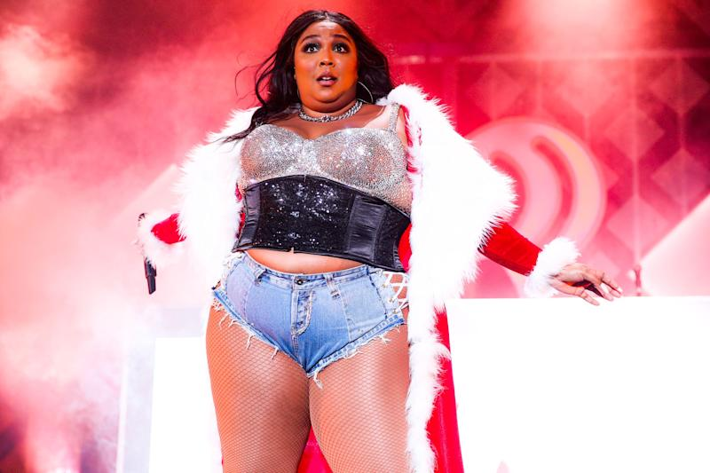 Lizzo stands on stage wearing a rhinetsone corset, jean shorts and a Santa Claus robe