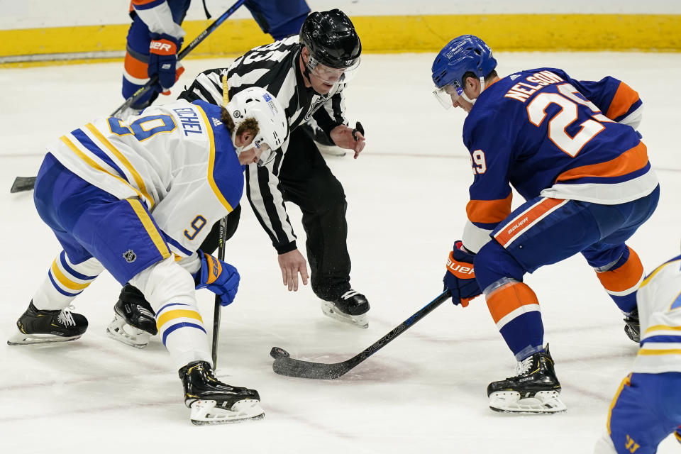 New York Islanders center Brock Nelson (29) wins a face-off against Buffalo Sabres center Jack Eichel (9) during the second period an NHL hockey game, Sunday, March 7, 2021, in Uniondale, N.Y. (AP Photo/John Minchillo)