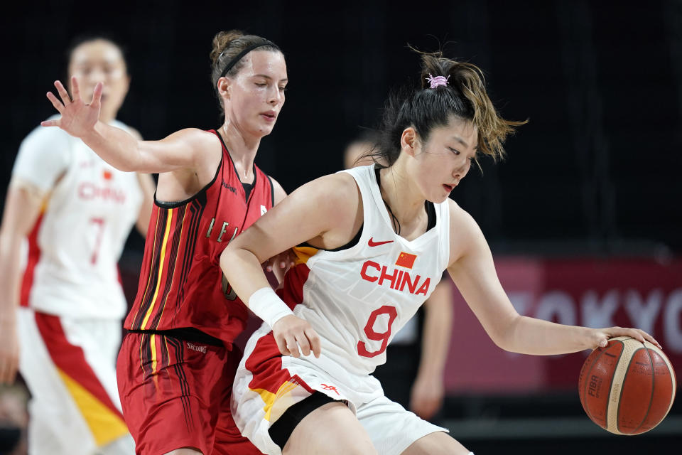 China's Meng Li (9) drives around Belgium's Antonia Delaere, left, during a women's basketball preliminary round game at the 2020 Summer Olympics, Monday, Aug. 2, 2021, in Saitama, Japan. (AP Photo/Charlie Neibergall)