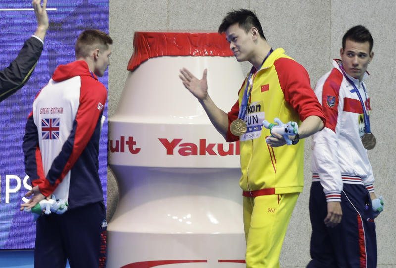 FILE - In this Tuesday, July 23, 2019 file photo, gold medalist China's Sun Yang, centre, gestures to Britain's bronze medalists Duncan Scott, left, following the medal ceremony in the men's 200m freestyle final at the World Swimming Championships in Gwangju, South Korea. Chinese swimmer Sun Yang has been banned for eight years for breaking anti-doping rules and will miss the 2020 Tokyo Olympics. (AP Photo/Mark Schiefelbein, File)