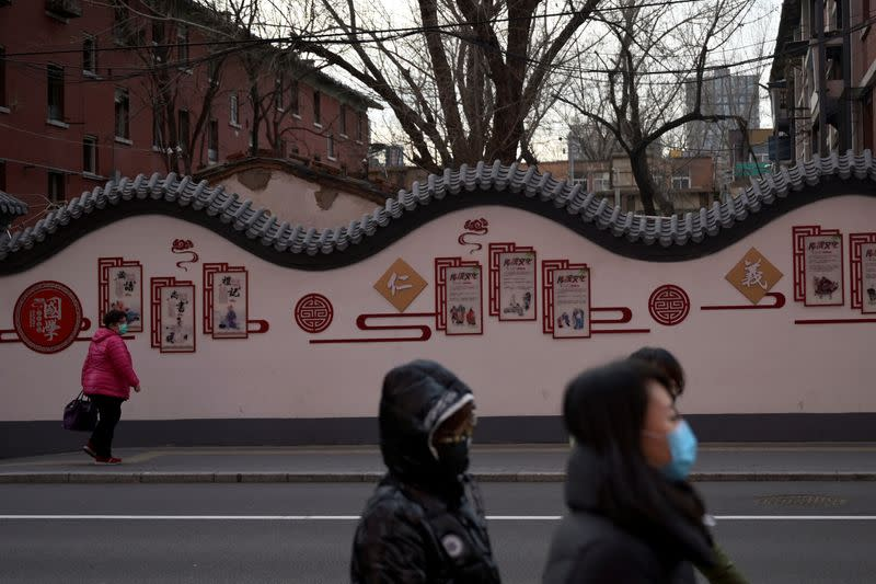 Pedestrians wearing face masks walk down the street in Beijing