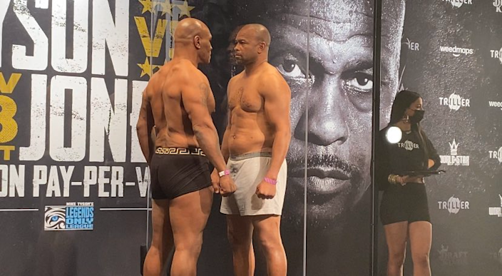 Mike Tyson, left, and Roy Jones Jr. have a stare down while separated by plexiglass after their weigh-in on Friday.